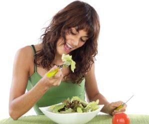 Pretty teenager eating salad over white background