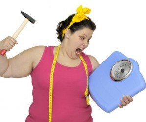 Angry large girl with hammer and scale isolated in white
