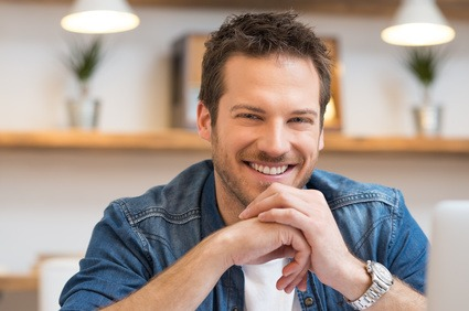 Closeup of smiling young businessman looking at camera in office